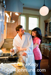 Romantic picture of a man fixing his wife breakfast at the kitchen stove with a frying pan. She is behind him with her arms around him.  He is wearing a white bath robe and she is dressed in a pink outfit.